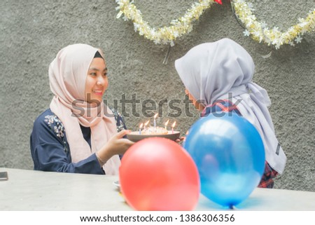 Portrait of two hijab woman bestfriend celebrate birthday with pancake and and light candle sitting on the cafe concrete table in day time -image