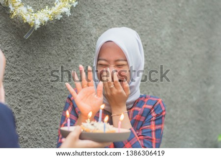 attractive hijab woman having surprise birthday cake from her bestfriend with candle while sitting on cafe -image