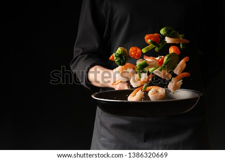 Seafood, Professional cook prepares shrimps with vegetables. Frost in the air, Cooking seafood, healthy vegetarian food and food on a dark background. Horizontal view. Eastern kitchen, banner #1386320669
