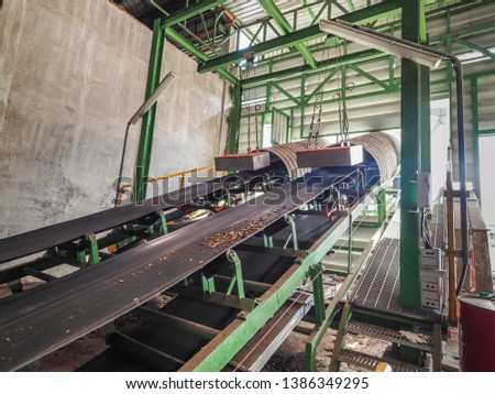 Belt conveyer of feed woof chipper fuel systems to boiler for product steam to steam turbine generator in biomass power plant. #1386349295