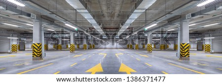 Empty shopping mall underground parking lot or garage interior with concrete stripe painted columns #1386371477