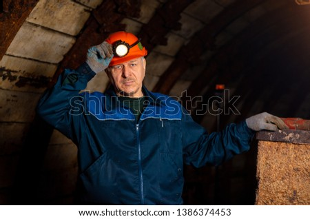 An elderly man dressed in work overalls and a hard hat is standing near the old caravan. Mine worker. Miner #1386374453