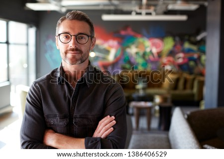 Middle aged white male creative in casual office lounge area looks to camera, arms crossed, waist up Royalty-Free Stock Photo #1386406529