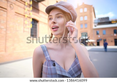 Cheerful woman talking on the phone in the street.  #1386416099