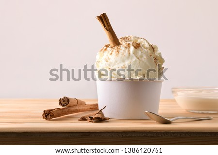 Cinnamon ice cream decorated with cinnamon sticks on a wooden table. Horizontal composition. Front view. #1386420761
