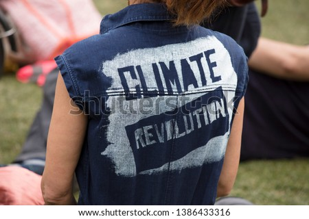 A climate change protestor wearing a top with climate revolution painted on #1386433316