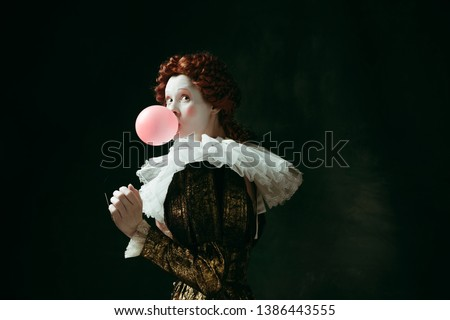 Medieval redhead young woman in golden vintage clothing as a duchess with red sunglasses blowing a bubblegum on dark green background. Concept of comparison of eras, modernity and renaissance. #1386443555