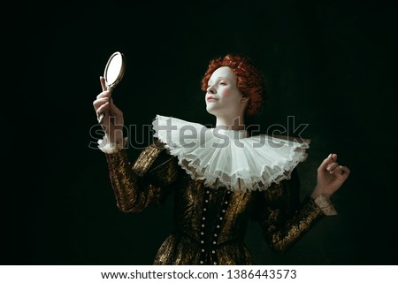 Proud of her self. Medieval redhead young woman in golden vintage clothing as a duchess looking in the mirror on dark green background. Concept of comparison of eras, modernity and renaissance. #1386443573