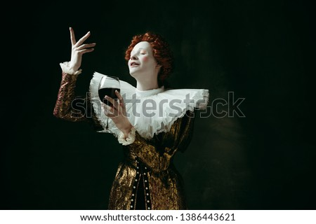 Drinks are an art. Medieval redhead young woman in golden vintage clothing as a duchess holding a glass with red wine on dark green background. Concept of comparison of eras, modernity and renaissance