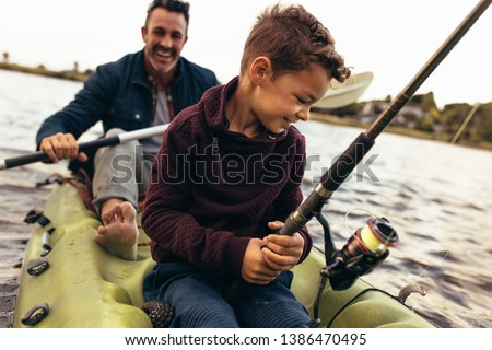 Close up of a kid sitting in a kayak catching fish holding a fishing rod. Happy man rowing a small boat in a lake while his kid tries to catch fish using a fishing rod. Royalty-Free Stock Photo #1386470495