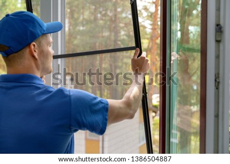 worker installing mosquito net wire mesh in plastic window frame Royalty-Free Stock Photo #1386504887