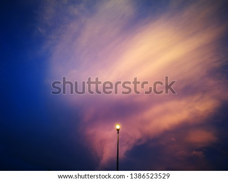 Selectively focused streetlight pole with view of sunset clouds #1386523529