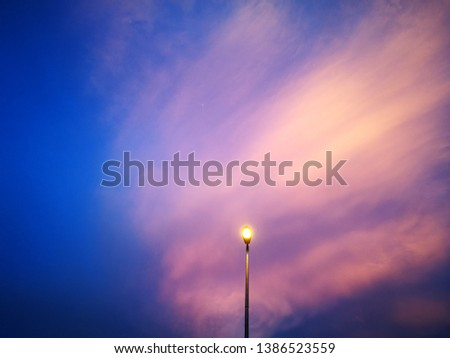 Selectively focused streetlight pole with view of sunset clouds #1386523559