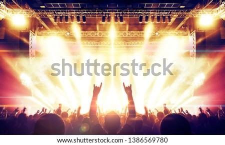 Raised hands in front of a concert stage for a festive crowd #1386569780