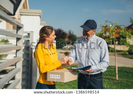 woman receiving package from post express delivery service #1386598514