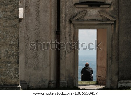 senior man sitting out of the chapel entrance - hope positive and calm spiritual concept - body copy negative space #1386658457