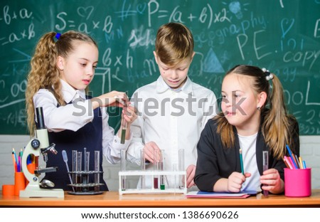 Test tubes with substances. Formal education. Girls and boy student conduct school experiment with liquids. School laboratory. Group school pupils study chemical liquids. School chemistry lesson. #1386690626