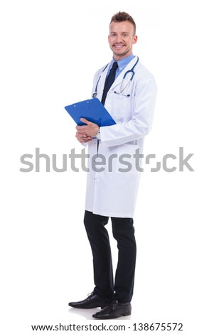 full body picture of a young doctor holding his notepad and  looking at the camera