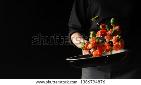 Sea cuisine, Professional cook prepares pieces of red fish, salmon, trout with vegetables.Cooking seafood, healthy vegetarian food and food on a dark background. Horizontal view. Banner #1386794876