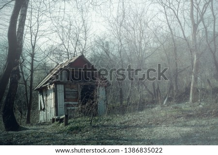 Abandoned hunting lodge in autumn forest. Dilapidated old wooden hut ruins in foggy wood, spooky landscape #1386835022