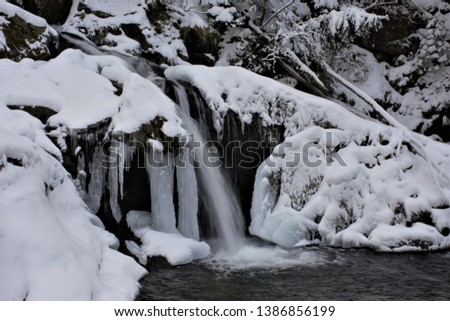 Winter waterfall on a mountain river among the ice pillars. #1386856199