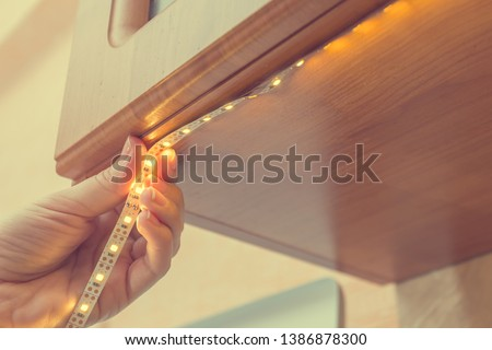 How to install led strip for lighting correctly on the surface of the Cabinet on the kitchen set Royalty-Free Stock Photo #1386878300