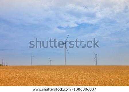 Wind turbine on a background of blue sky #1386886037