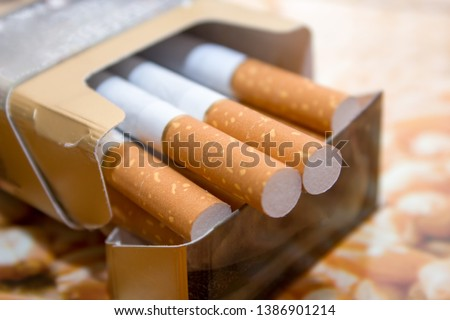 Cigarettes in a pack. Yellow filter. Harm to health. Bad habit. A pack of cigarettes on the table. open pack of cigarettes. #1386901214