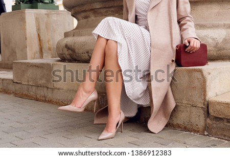 Closeup fashionable woman legs wear beige high heel shoes, dress and sitting. Outdoor fall and spring outfit Royalty-Free Stock Photo #1386912383