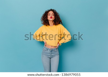 Coquettish woman dressed in bright cropped sweater and jeans blows kiss. Portrait of curly girl with red lipstick #1386979055