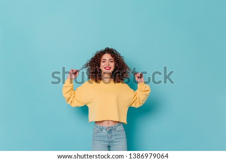 Charming lady in yellow sweater and skinny jeans smiles and touches her curly dark hair against blue background