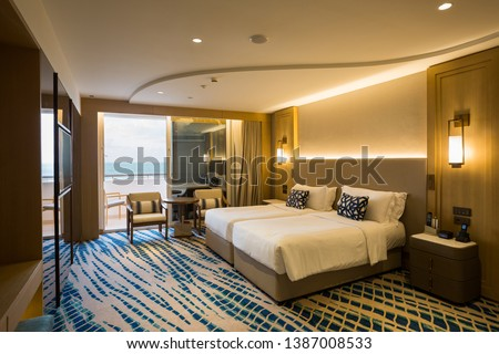 Hotel room interior. Modern hotel. Seaside resort. Sea view. Bedroom interior. Cozy bedroom. Big double bed. Bedroom furniture.  #1387008533