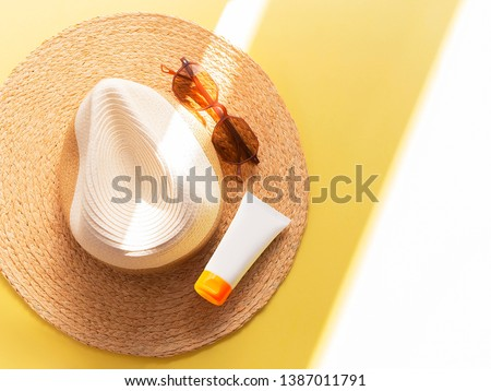 Sunprotection objects. Straw woman's hat with sun glasses and protection cream spf 30 top view on bright yellow background. Beach accessories. Summer Travel Vacation Concept. Sale kit. Copy space.  #1387011791