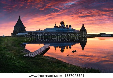 Pink sunset view on the lake with a view of the Solovetsky Monastery. Russia, Arkhangelsk region, White sea, Solovki (iconic view, Solovki Kremlin). Famous Russian Landmark Of North.  #1387023521