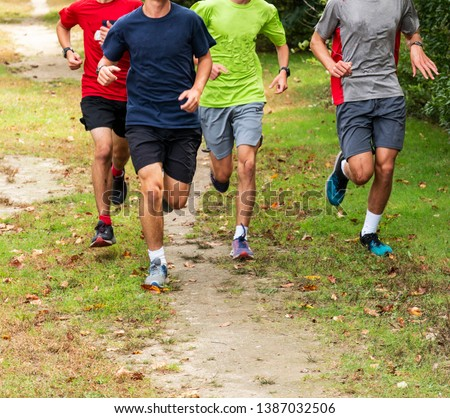 High school cross country boys are running in a group during a training run on a dirt and grass path in a local park. #1387032506