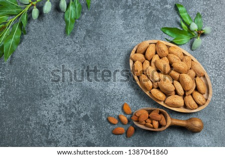 Top view Almond nuts in wooden shovel, almonds with shell in bamboo bowl on grey rustic table with green fresh raw almonds on almond tree branch. Almond background concept with copy space #1387041860