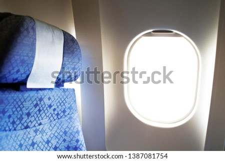 Comfortable aircraft seats with headrest by the window. Royalty-Free Stock Photo #1387081754