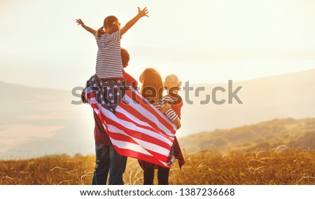 happy family with the flag of america USA at sunset outdoors #1387236668
