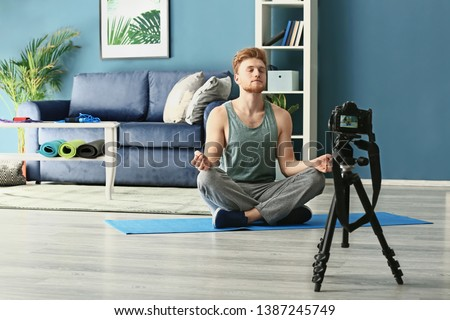 Young male sport blogger recording video at home #1387245749