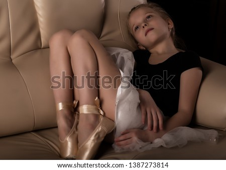 little ballerina in pointe sits and resting on the sofa. cute ballerina in the dance class is studying ballet. Classical dance, ballet #1387273814