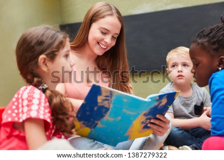 Group of children and educators reading from a children's book or storybook #1387279322