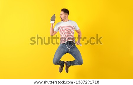 Jumping young man with iron on color background