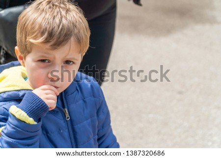 Young boy eating popcorn at an outdoors park #1387320686