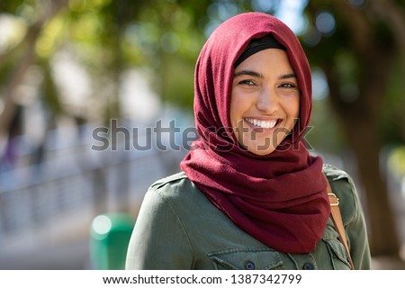 Portrait of young muslim woman wearing hijab head scarf in city while looking at camera. Closeup face of cheerful woman covered with headscarf smiling outdoor. Casual islamic girl at park. Royalty-Free Stock Photo #1387342799