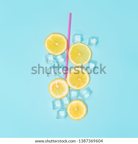 Creative summer background composition with lemon slices, straw and ice cubes. Minimal top down lemonade drink concept. #1387369604