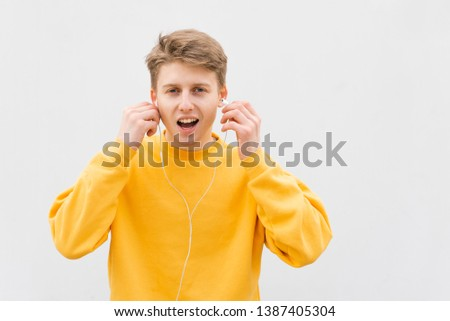 Portrait of an emotional young man in a yellow sweatshirt on background of a white wall in the headphones,looks surprised in camera,open mouth.Stylish teenager listens to music on a white background #1387405304