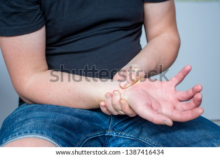 Pain in wrist of hand concept photo. Man grabbed his hand by wrist of other hand due to occurrence of severe pain in area due to carpal tunnel syndrome, nerve block, skin numbness and other diseases