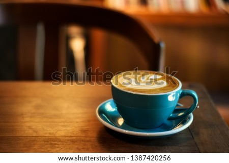 Coffee in blue cup on wooden table in cafe with lighting background #1387420256