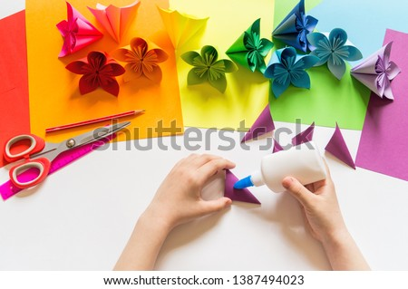 Hands of the girl origami puts flowers from paper of Violet trend color. Flat lay style. rainbow color #1387494023