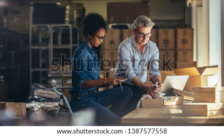 Man packing the product in the box with woman preparing the invoice. Two people working together at warehouse for online seller business. #1387577558